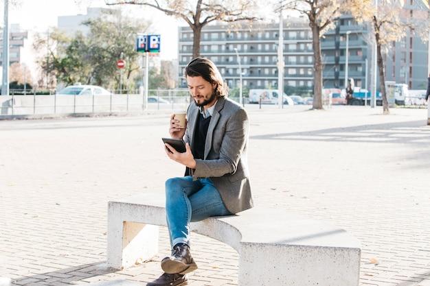 Hombre joven que se sienta en el parque de la ciudad que mira el teléfono móvil que sostiene la taza de café para llevar
