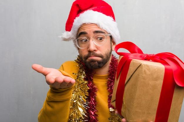 Hombre joven que se sienta con los regalos que celebran la navidad confundida y dudosa