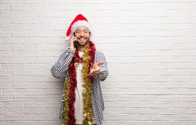 Hombre joven que se sienta con los regalos que celebran la navidad que alcanza hacia fuera para saludar a alguien