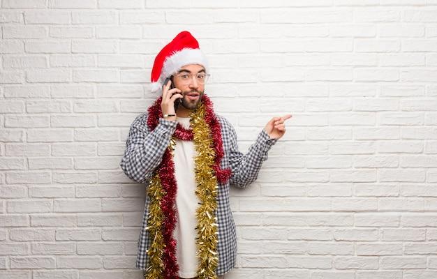 Hombre joven que se sienta con los regalos que celebran la navidad que señala al lado con el finger