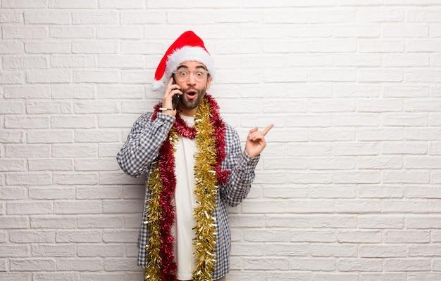 Hombre joven que se sienta con los regalos que celebran la navidad que señala al lado