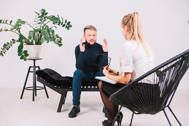Hombre joven que se sienta en el sofá que discute con el psicoterapeuta de sexo femenino sus problemas