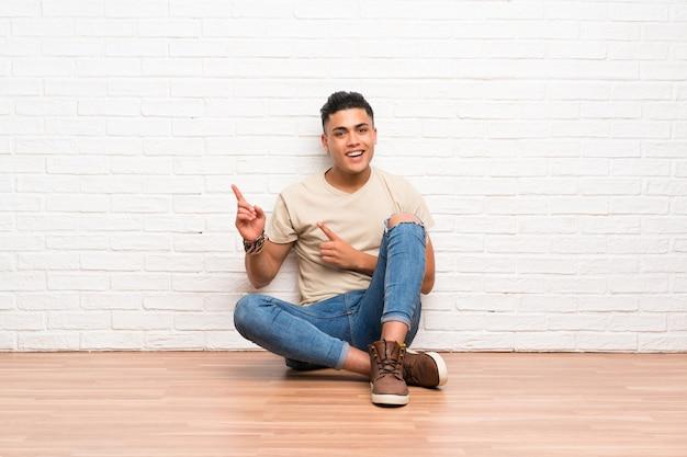 Hombre joven que se sienta en el suelo que señala el dedo al lado