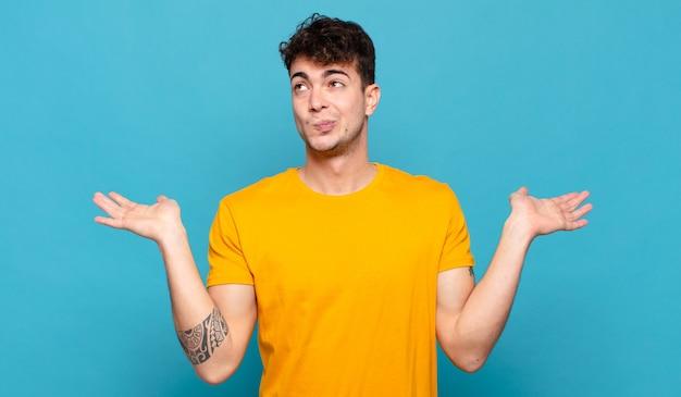 Hombre joven que se siente desconcertado y confundido, dudando, ponderando o eligiendo diferentes opciones con expresión divertida