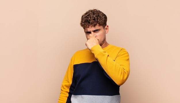 Hombre joven que se siente disgustado, tapándose la nariz para evitar oler un hedor desagradable y desagradable