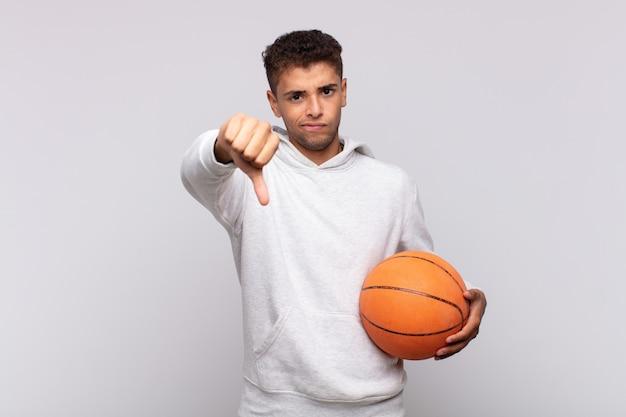 Hombre joven que se siente enfadado, enojado, molesto, decepcionado o disgustado, mostrando el pulgar hacia abajo con una mirada seria.