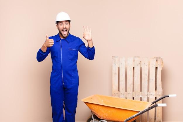 Hombre joven que se siente feliz, asombrado, satisfecho y sorprendido, mostrando gestos de aprobación y pulgar hacia arriba, concepto de construcción sonriente