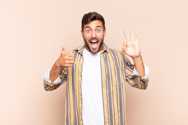 Hombre joven que se siente feliz, asombrado, satisfecho y sorprendido, mostrando gestos de aprobación y pulgar hacia arriba, sonriendo