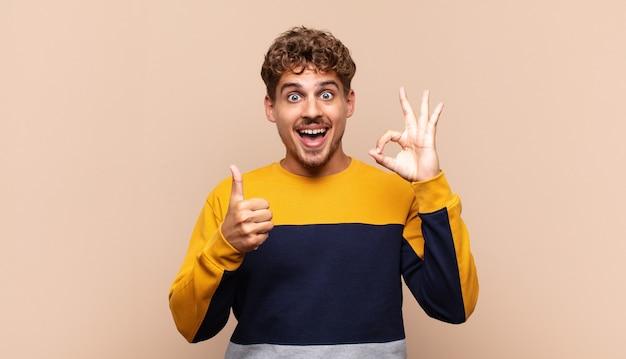 Hombre joven que se siente feliz, asombrado, satisfecho y sorprendido, mostrando gestos de aprobación y pulgar hacia arriba