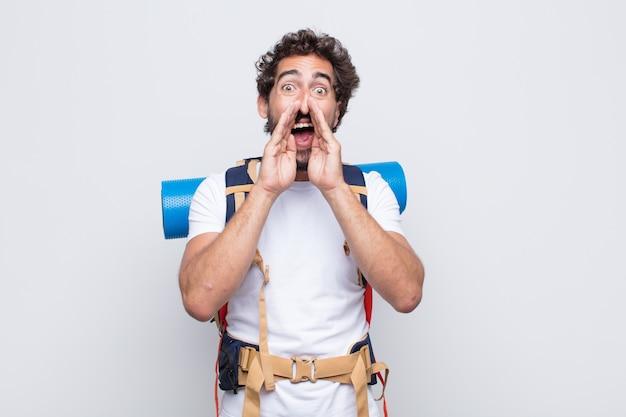 Hombre joven que se siente feliz, emocionado y positivo, dando un gran grito con las manos al lado de la boca, gritando
