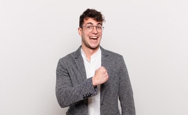 Hombre joven que se siente feliz, positivo y exitoso, motivado cuando enfrenta un desafío o celebra buenos resultados.