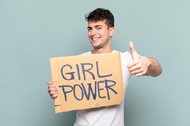 Hombre joven que se siente orgulloso, despreocupado, seguro y feliz, sonriendo positivamente con los pulgares hacia arriba