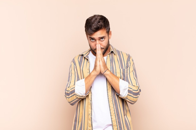 Hombre joven que se siente preocupado, esperanzado y religioso, orando fielmente con las palmas presionadas, pidiendo perdón