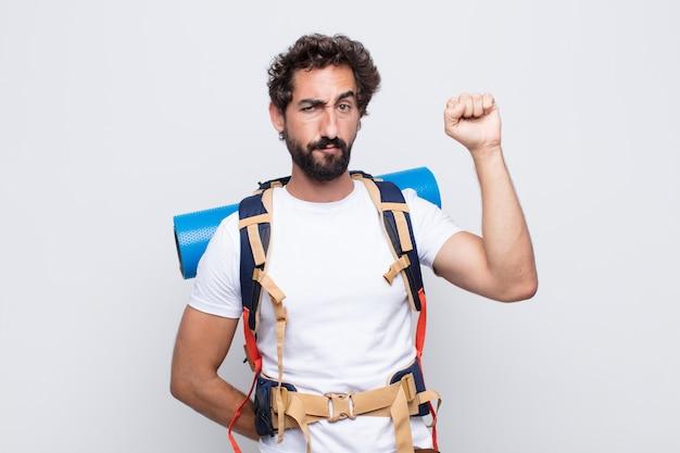 Hombre joven que se siente serio, fuerte y rebelde, levanta el puño, protesta o lucha por la revolución