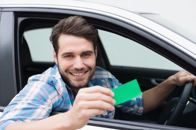 Hombre joven que sonríe en la cámara que muestra la tarjeta