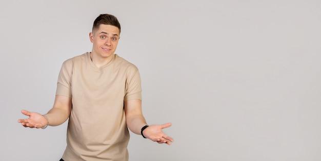 El hombre joven que sonríe y extiende las manos no sabe qué decir en respuesta