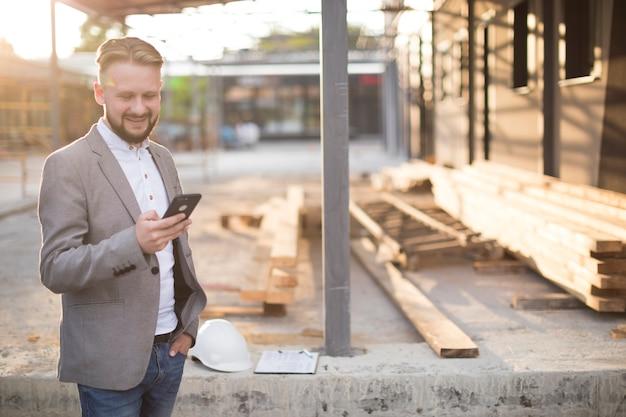 Hombre joven que sonríe mientras que usa el teléfono móvil en el emplazamiento de la obra