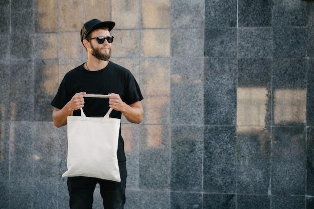 Hombre joven que sostiene la bolsa ecológica textil blanca contra el fondo urbano de la ciudad. . concepto de protección de la ecología o el medio ambiente. bolsa ecológica blanca para maqueta.
