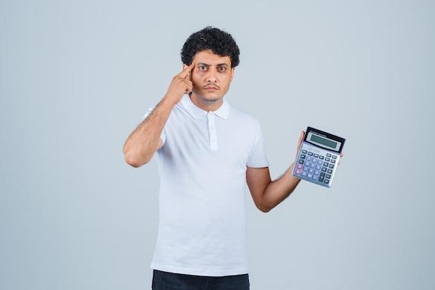 Hombre joven que sostiene la calculadora mientras mantiene el dedo en las sienes en camiseta blanca y parece inteligente. vista frontal.