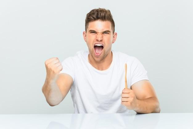 Hombre joven que sostiene un cepillo de dientes que anima despreocupado y emocionado. victoria