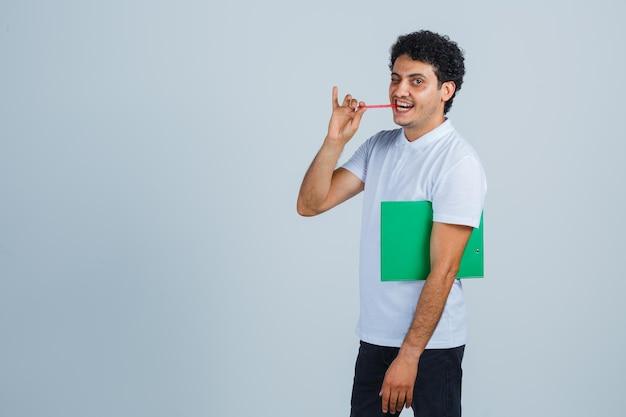 Hombre joven que sostiene el cuaderno y el bolígrafo, mordiendo el bolígrafo mientras mira a la cámara en camiseta blanca y jeans y parece feliz. vista frontal.