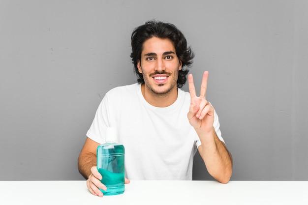 Hombre joven que sostiene un enjuague bucal que muestra el número dos con los dedos.
