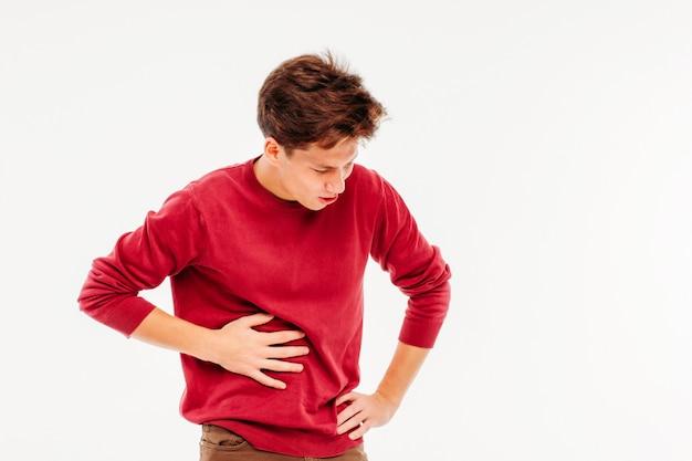 Hombre joven que sostiene el hígado, experimentando dolor, en el fondo blanco