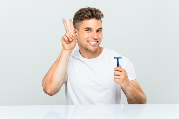 Hombre joven que sostiene una hoja de afeitar que muestra la muestra de la victoria y que sonríe ampliamente.