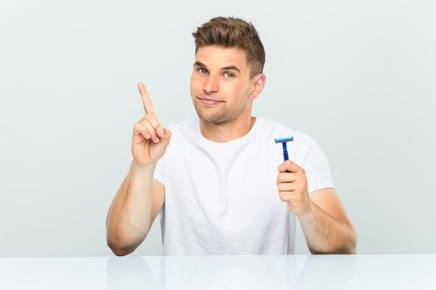 Hombre joven que sostiene una hoja de afeitar que muestra el número uno con el dedo.