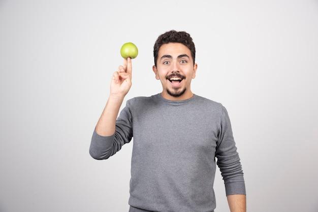 Hombre joven que sostiene la manzana verde felizmente.