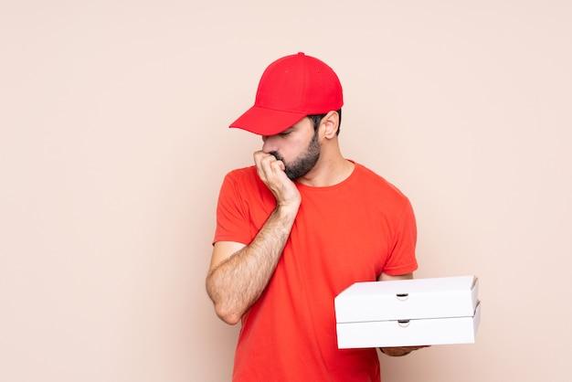 Hombre joven que sostiene una pizza sobre aislado que tiene dudas