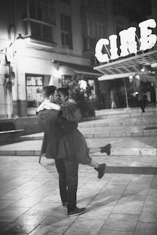 Hombre joven que se sostiene y que gira con la mujer de risa en la calle