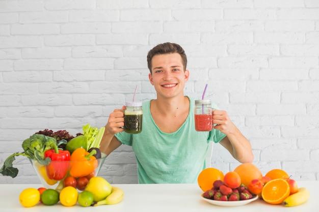 Hombre joven que sostiene el smoothie verde y rojo en su mano con la comida sana en la tabla