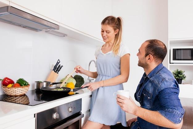Hombre joven que sostiene la taza de café en la mano que mira a su esposa sonriente que cocina la comida en la cocina