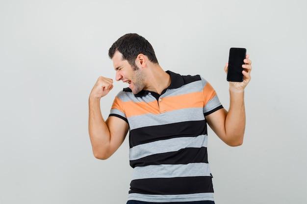 Hombre joven que sostiene el teléfono móvil mientras muestra el gesto del ganador en la camiseta y parece enérgico.