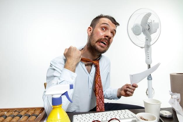 Hombre joven que sufre del calor en la oficina