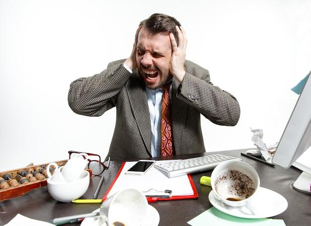 Hombre joven que sufre de las conversaciones de los colegas en la oficina