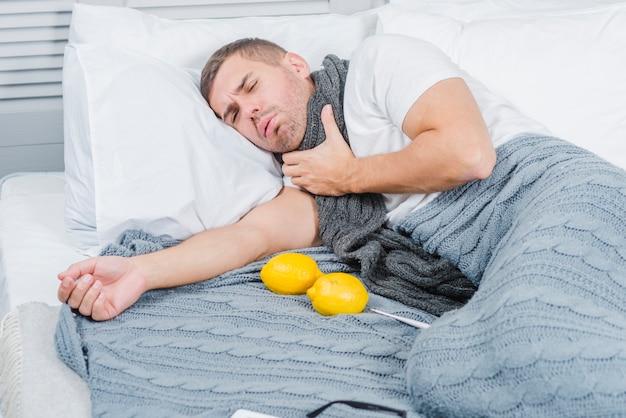 Hombre joven que sufre de dolor de garganta acostado en la cama con limón y termómetro