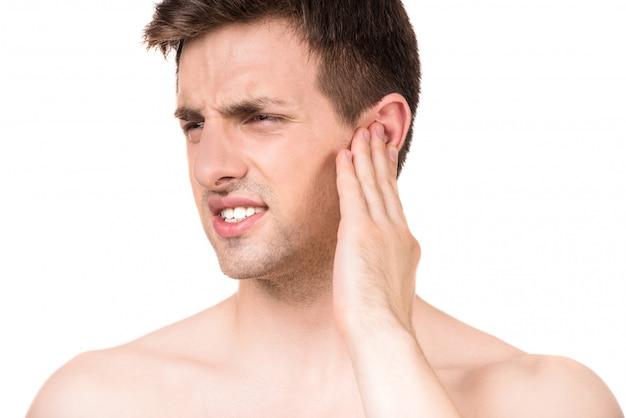 Hombre joven que sufre del dolor que cierra el oído con la mano.