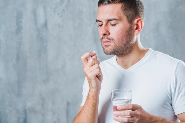 Un hombre joven que tiene píldora blanca con vaso de agua contra el muro de hormigón