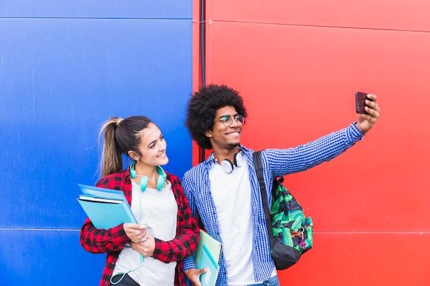 Hombre joven que toma selfie con su novia sosteniendo libros en la mano en el teléfono móvil contra la pared roja y azul