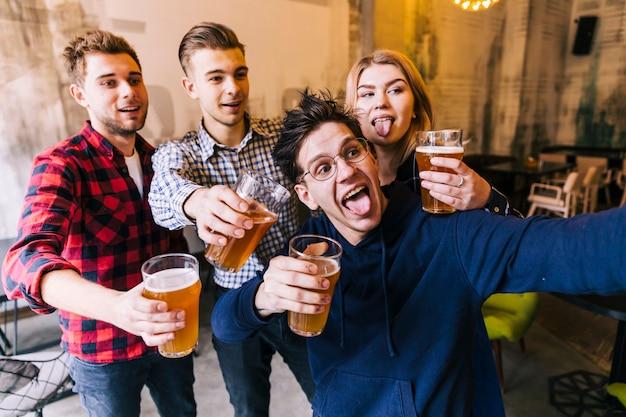 Hombre joven que toma selfie en el teléfono móvil con sus amigos sosteniendo los vasos de cerveza
