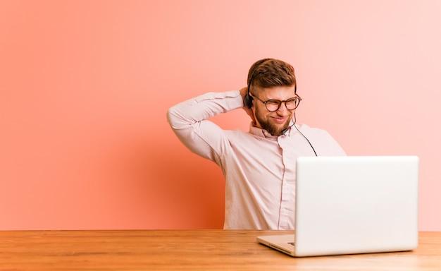 Hombre joven que trabaja en un call center que sufre dolor de cuello debido al estilo de vida sedentario.