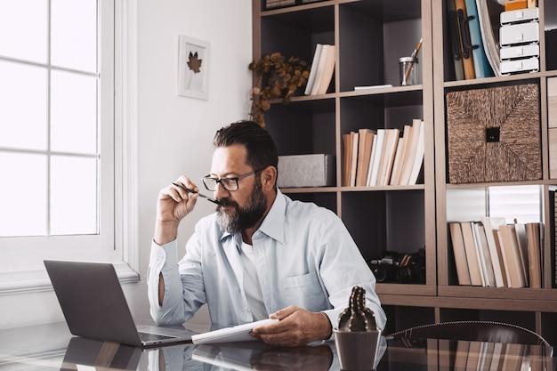 Un hombre joven que trabaja en casa en la oficina con una computadora portátil y un cuaderno tomando notas hablando en una videoconferencia. un empresario llamando a comunicarse