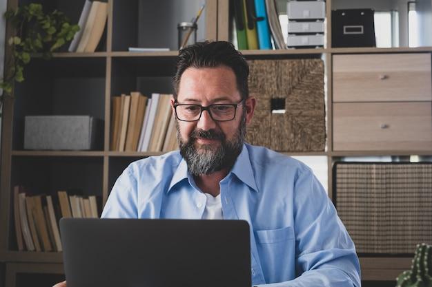 Un hombre joven que trabaja en casa en la oficina con un portátil y un portátil hablando en una videoconferencia. un empresario llamando a comunicarse