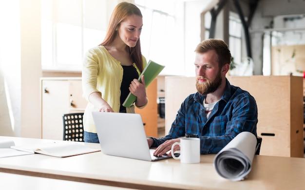Hombre joven que trabaja en la computadora portátil con los colegas en el escritorio en oficina