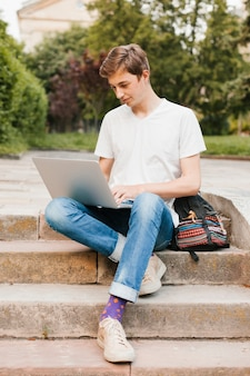 Hombre joven que trabaja en la computadora portátil en el parque