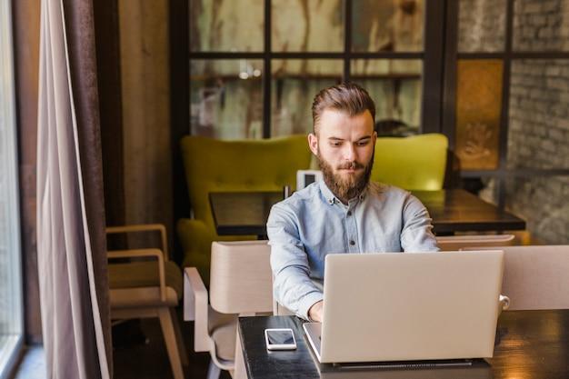 Hombre joven que trabaja en la computadora portátil en el restaurante