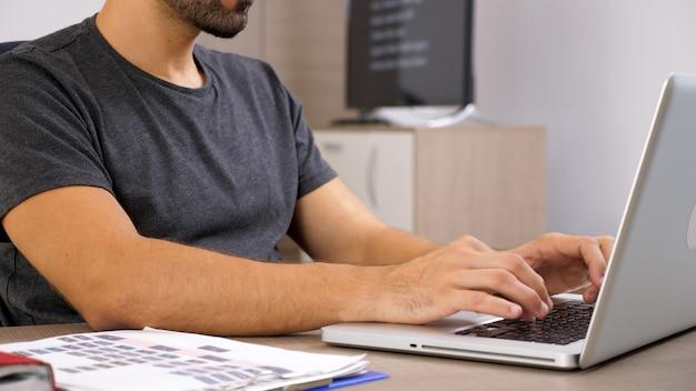 Hombre joven que trabaja con el portátil en la documentación de su empresa. persona de negocios en el lugar de trabajo.
