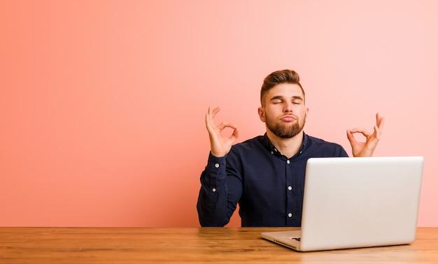 El hombre joven que trabaja con su computadora portátil se relaja después del día laborable duro, él está realizando yoga.